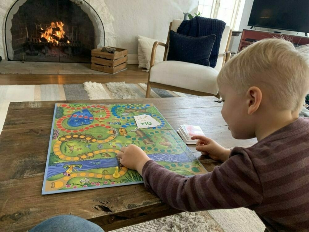 Photo of my son playing a board game with a fire burning in the background