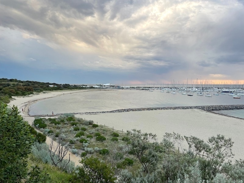 a view overlooking a beach, with light grey-blue water and cloudy skies with some peach-coloured sky on the horizon