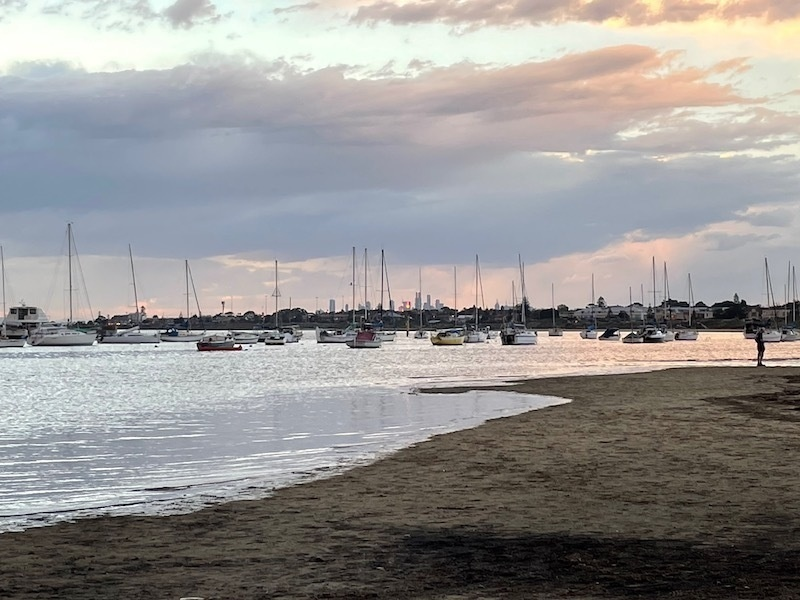 a view on the beach; a bunch of boats are floating in the water, the sky has got more pink, and in the distance sunlight is reflecting off towers in the distant city