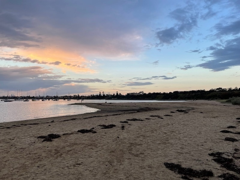 a view on the beach. a dark grey cloud to the left in the sky, with light blue and pink around it