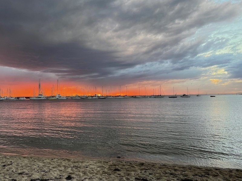 a view from a little later on the beach. the grey cloud is now larger and more dominant; on the horizon is a darker pink, almost red