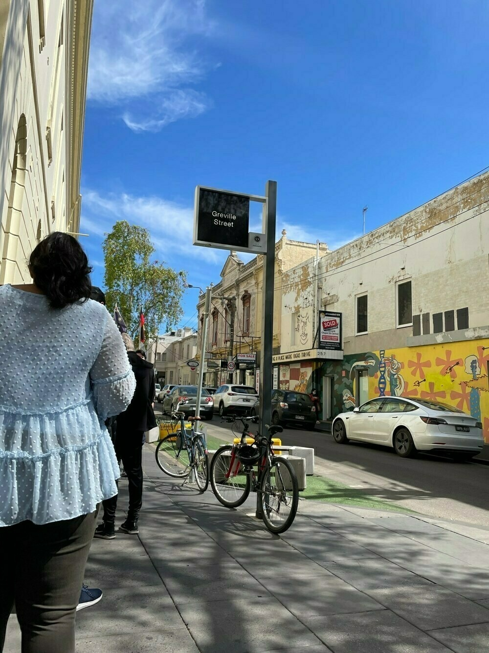 Greville St Prahran, with a queue of waiting people, a mural and a road devoid of traffic