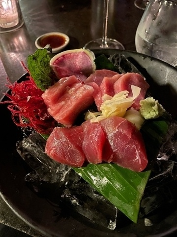 Sashimi with three kinds of tuna on banana leaf and ice.